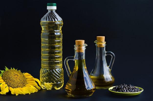 Flasche und krug mit raffiniertem und nicht raffiniertem sonnenblumenöl, gelber blume und samen.