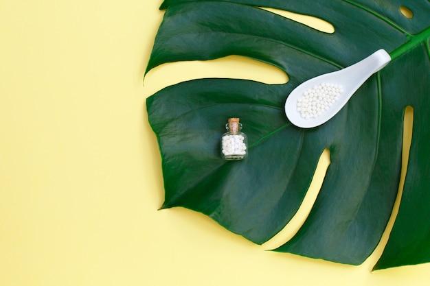 Flasche und löffel mit homöopathischen pillen auf palmblatt.
