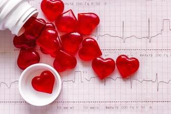 Flasche und Streuung von Figuren in Form von roten Herzen