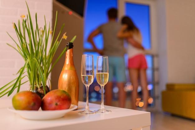 Flasche und zwei gläser champagner auf couchtisch im wohnzimmer