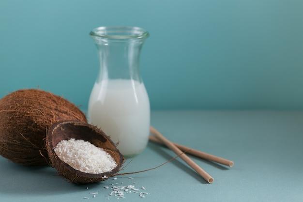 Flasche vegane kokosmilch mit strohhalmen, ganzer kokosnuss und flocken auf hellblauem hintergrund. gesundes lebensstilkonzept.