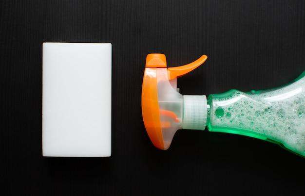 Flasche waschmittel ein weißer melaminschwamm auf schwarzem hintergrund