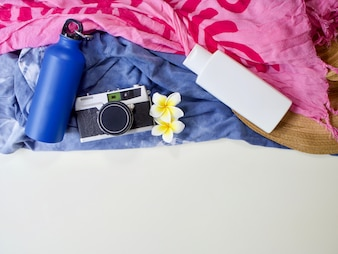 Flasche Wasser, Filmkamera, weiße Plumeria-Blumenlage und weiße Flasche mock-up auf Farbe