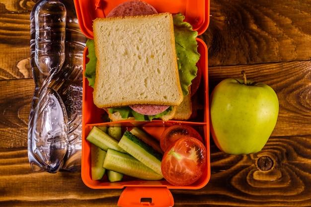 Flasche wasser, grüner apfel und brotdose mit sandwich, gurken und tomaten auf rustikalem holztisch. ansicht von oben