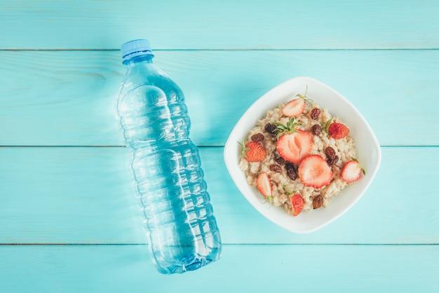 Flasche wasser, haferflocken mit erdbeeren und rosinen auf blauer, flacher lage