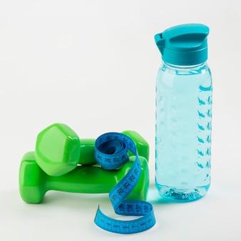 Flasche wasser mit blauem zentimeter und gewichten