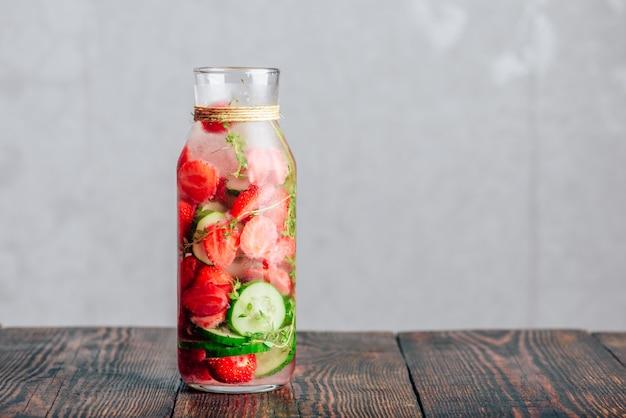 Flasche wasser mit frischer erdbeere