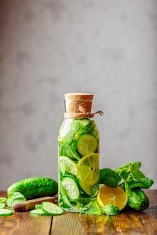 Flasche wasser mit geschnittenen zitronen-, gurken- und minzblättern. zutaten und messer auf dem tisch.