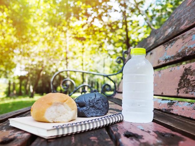 Flasche wasser und selbst gemachtes brot auf weinlesebank im park.