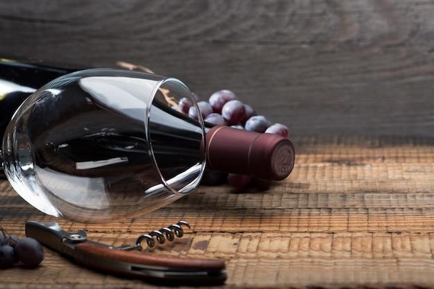 Flasche wein, ein glas, eine weintraube und weinblätter auf einem alten holztisch.