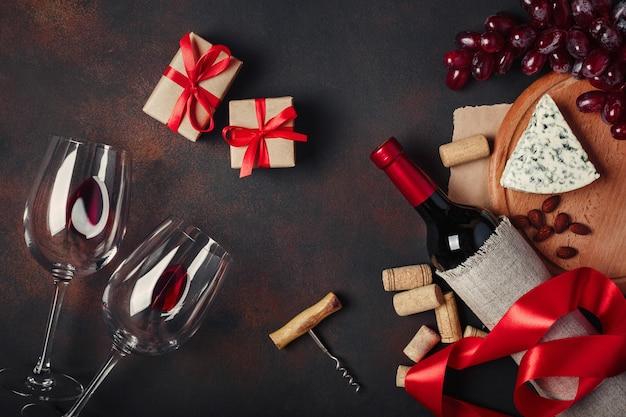 Flasche wein, geschenkbox, rote trauben, mandeln, korkenzieher und korken, draufsicht