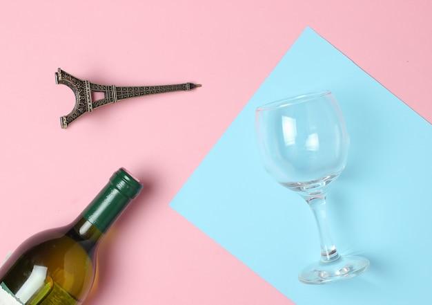 Flasche wein, glas, statuette des eiffelturms auf einer farbigen pastelloberfläche. draufsicht. minimalismus