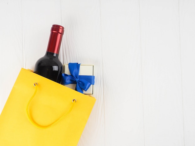 Flasche wein im paket mit einem geschenk, draufsicht