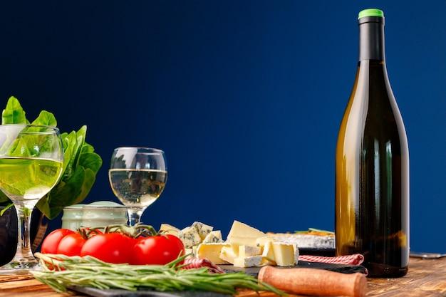 Flasche wein mit geschnittenem käse und tomaten auf tisch vor blauem hintergrund