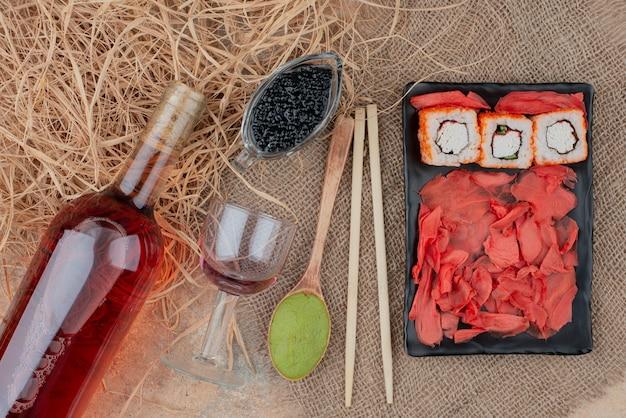 Flasche wein mit weinglas und sushi auf sackleinen