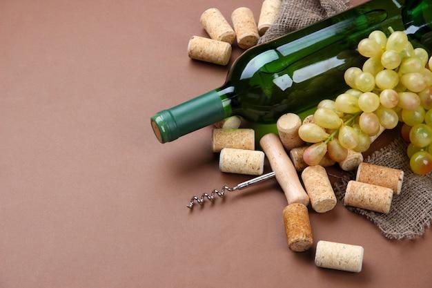 Flasche wein, trauben und korken auf braun
