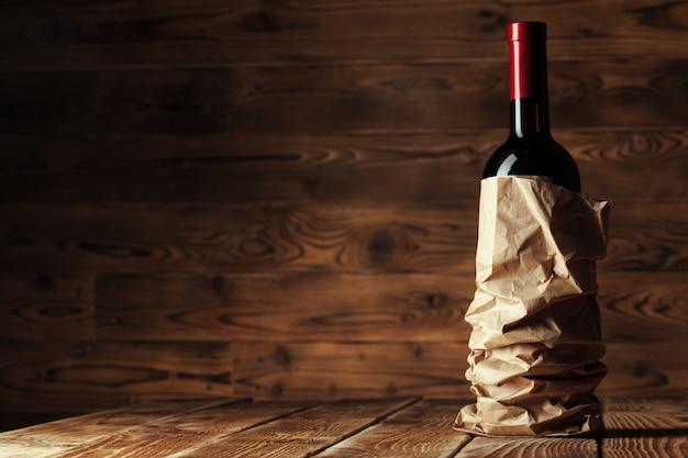 Flasche wein über hölzernen hintergrund