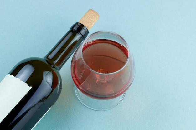 Flasche wein und weinglas mit draufsicht des rotweins über blauen hintergrund