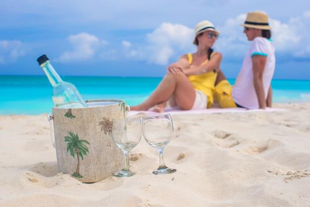 Flasche wein und zwei glückliches paar des glashintergrundes am strand