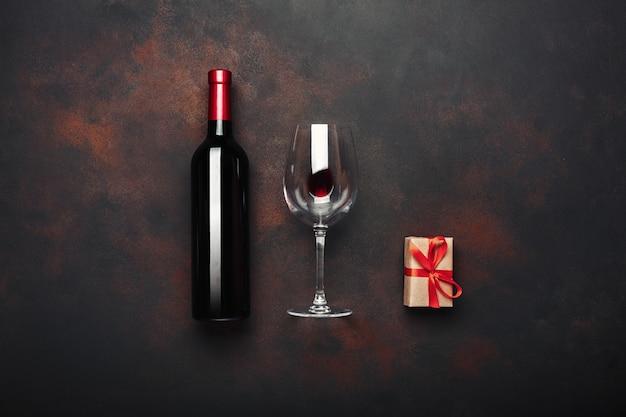 Flasche weingeschenkboxkorkenzieher und -weinglas auf rostigem hintergrund