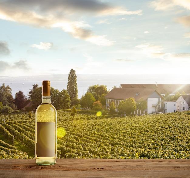 Flasche weißwein auf holzschiene mit ländlicher landschaft im hintergrund grün
