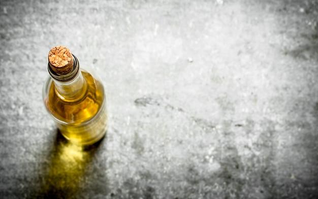 Flasche weißwein auf steintisch.