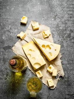 Flasche weißwein mit duftenden käsescheiben. auf dem steintisch.