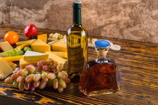 Flasche weißwein und bernstein-whisky-alkohol auf rustikalem holztisch mit verschiedenen gourmet-käse und trauben - zutaten für käsebrett