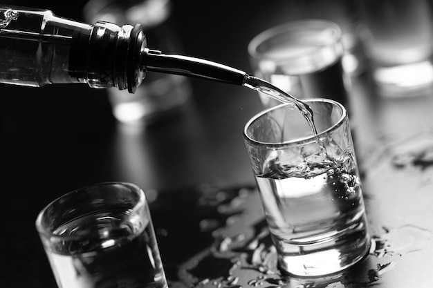 Flasche wodka und in einer schnapsglas-nahaufnahme.
