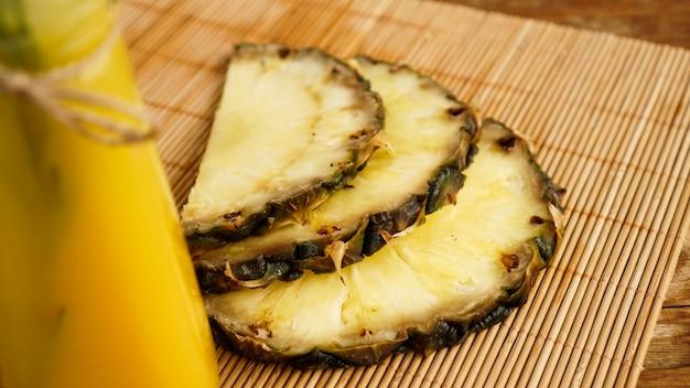 Flaschen ananassaft auf einem holztisch. gelbes getränk und frische ananas. snack im resort. sommerfoto