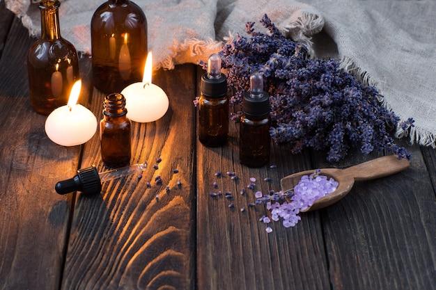 Flaschen aromaöl, kerzen, meersalz in einem holzlöffel und lavendelblüten