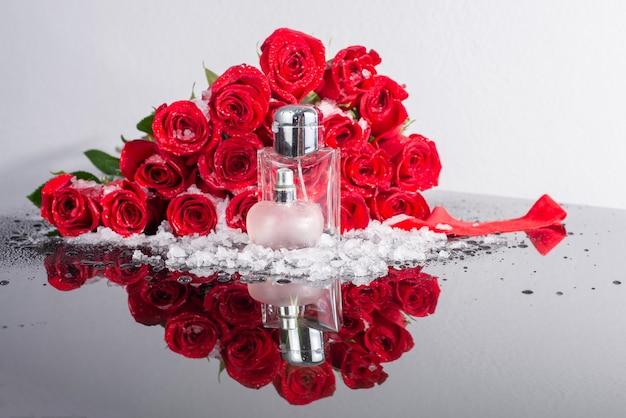 Flaschen männliches und weibliches parfüm auf einem hintergrund von roten rosen und schnee.