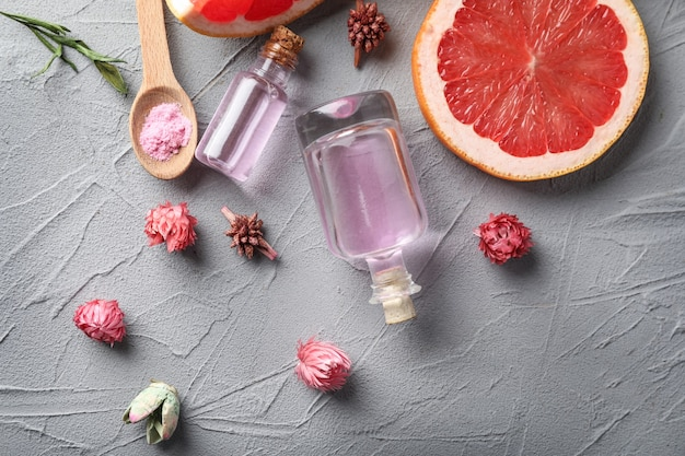 Flaschen mit ätherischem zitrusöl und geschnittenen früchten auf grau