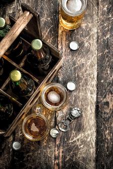 Flaschen mit bier in einer alten schachtel auf holztisch.