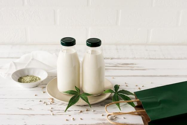 Flaschen mit cannabis pflanzlichem veganem gluten und laktosefreier milch und cannabisblättern auf holztisch.