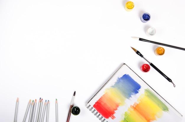 Flaschen mit farbe und pinsel mit farbigem notizblock