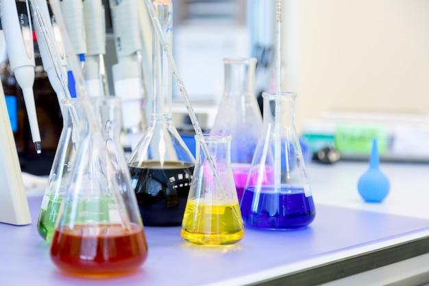 Flaschen mit farbigen flüssigen reagenzien in einem wissenschaftslabor.