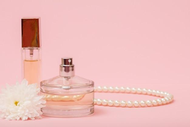 Flaschen mit frauenparfüm, perlen und blütenknospe in rosafarbenem hintergrund mit kopierraum. produkte für frauen.