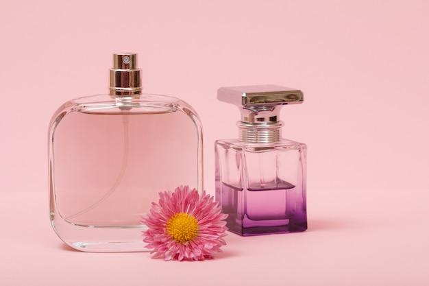 Flaschen mit frauenparfüm und blütenknospe in rosafarbenem hintergrund. produkte für frauen.