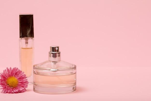 Flaschen mit frauenparfüm und blumenknospe in einem rosafarbenen hintergrund mit kopienraum. produkte für frauen.