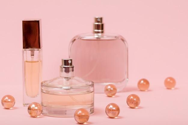 Flaschen mit frauenparfüm und dekorativen glaskugeln auf rosafarbenem hintergrund. produkte für frauen.