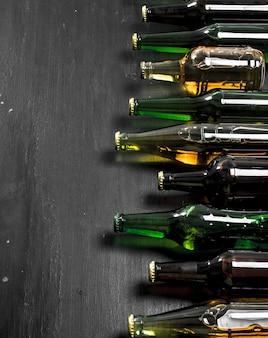 Flaschen mit frischem bier auf schwarzer tafel.