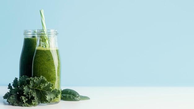Flaschen mit grünem smoothie und kopierraum