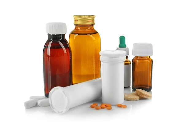 Flaschen mit hustensaft, pillen und medikamenten isoliert auf weiß