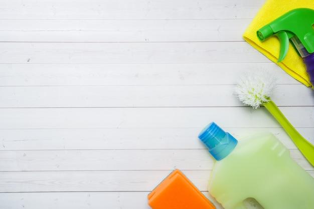 Flaschen mit reinigungsmitteln, bürsten und schwämmen auf hölzernem hintergrund.