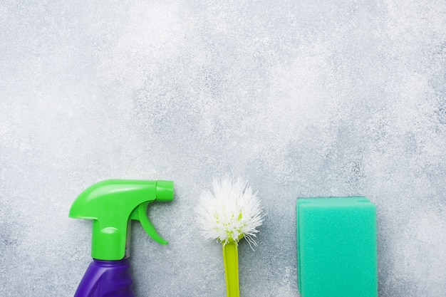Flaschen mit reinigungsmitteln, bürsten und schwämmen auf konkretem hintergrund.