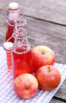 Flaschen mit roten getränken und einigen äpfeln