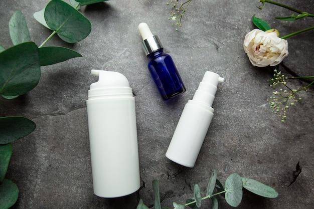 Flaschen mit serum und gläsern mit kosmetischen cremes auf grauem hintergrund mit eukalyptuszweigen und grün