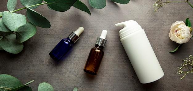Flaschen mit serum und gläsern mit kosmetischen cremes auf grauem hintergrund mit eukalyptuszweigen