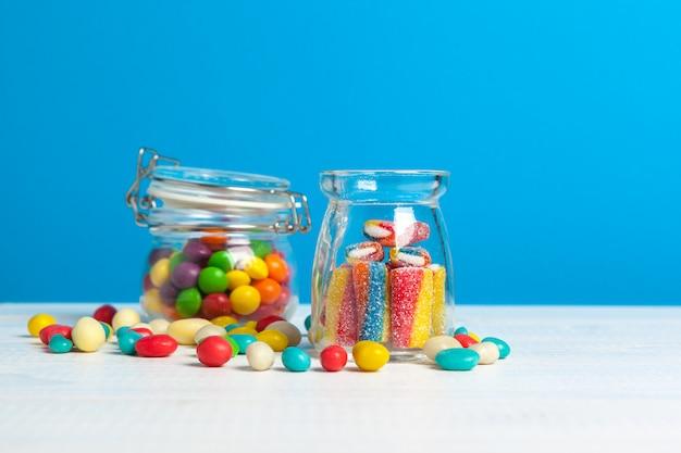Flaschen mit süßen süßigkeiten auf tabelle